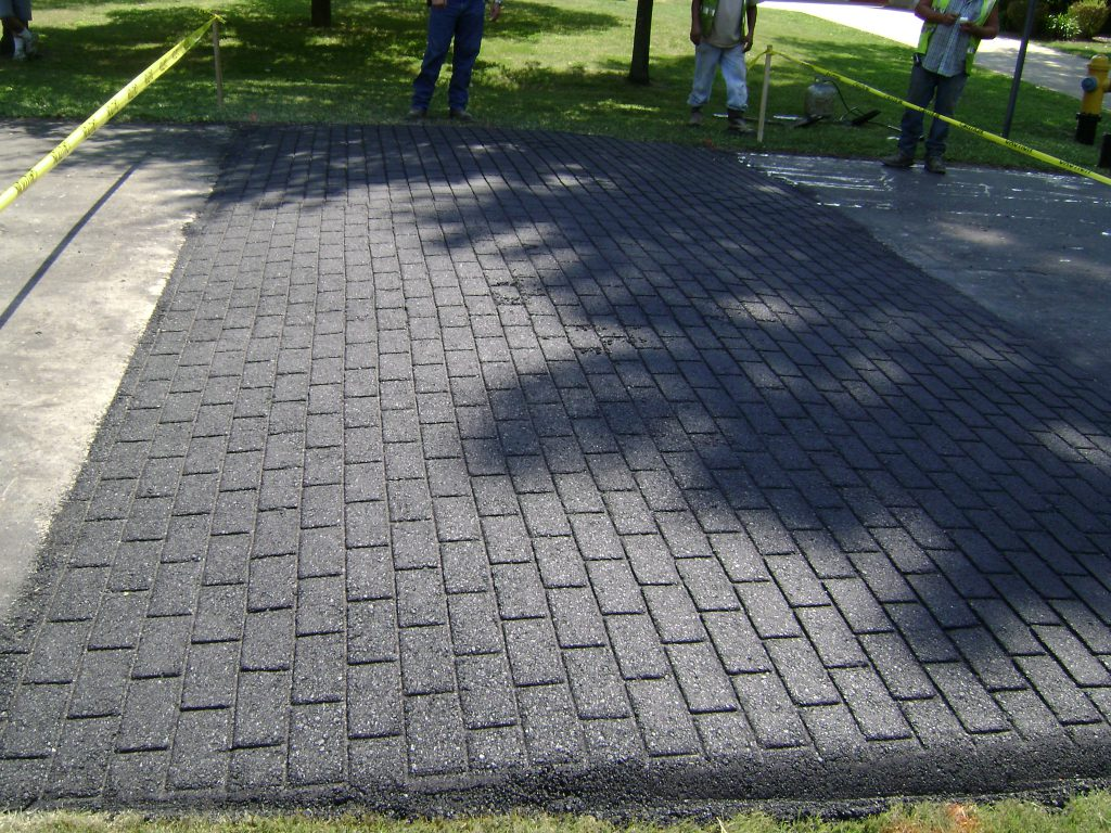 Driveway contractor installed blacktop driveway stamped to look like brick by a residential paving contractor.